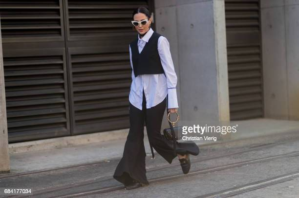 A guest wearing a black vest white button shirt flared pants Chloe bag at day 4 during MercedesBenz Fashion Week Resort 18 Collections at...
