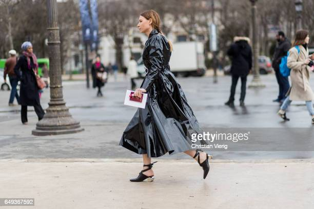 A guest wearing a black vinyl coat outside Chanel on March 7 2017 in Paris France