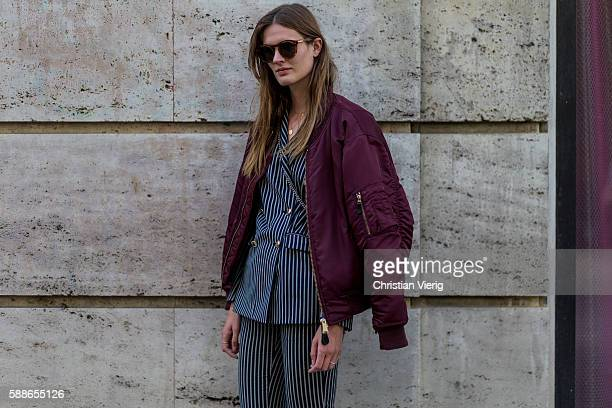 A guest wearing a black white striped suit and bordeaux bomber jacket outside Baum und Pferdgarten during the second day of the Copenhagen Fashion...