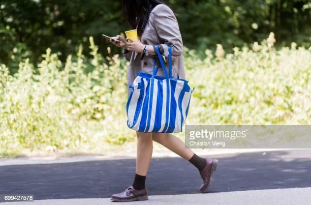 A guest wearing a blazer jacket blue white striped Balenciaga bag leather shoes socks outside Balenciaga during Paris Fashion Week Menswear...