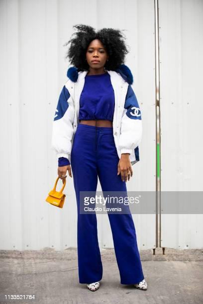 A guest wearing a blu cropped sweatshirt blue pants white and blue Chanel bomber jacket white printed heels and yellow bag is seen outside Balenciaga...