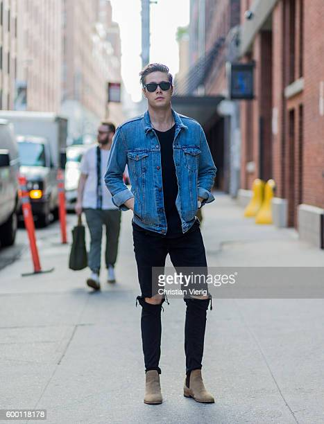 A guest wearing a blue denim jacket black ripped jeans and Chelsea boots outside Parsons on September 7 2016 in New York City