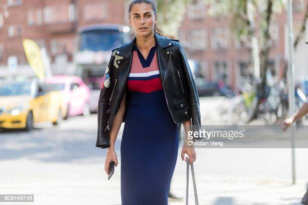 A guest wearing a blue dress black leather jacket outside Munthe on August 09 2017 in Copenhagen Denmark