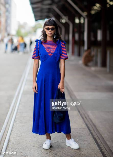 A guest wearing a blue dress velvet bag blue red striped tshirt during MercedesBenz Fashion Week Resort 19 Collections at Carriageworks on May 15...
