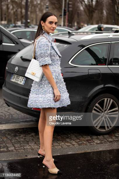 A guest wearing a blue mini dress nude and black Chanel heels and white Chanel bag is seen outside Chanel on Day 9 Paris Fashion Week Autumn/Winter...