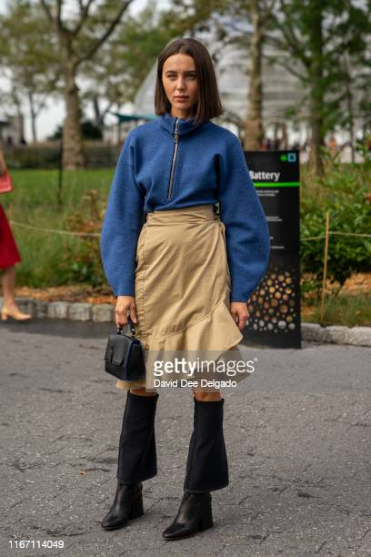 Guest wearing a blue quarter-zip pullover, khaki wrap skirt, and black knee-high boots attends the Carolina Herrera show during New York Fashion Week...