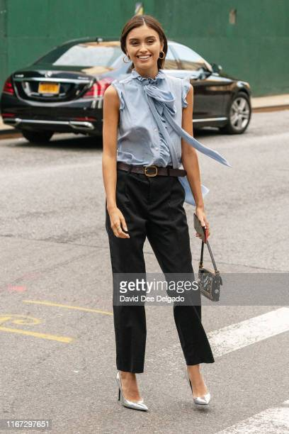 A guest wearing a blue ruffle blouse black pants and a black belt is seen outside Coach 1941 during New York Fashion Week on September 10 2019 in New...