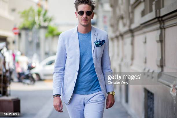 Guest wearing a blue shirt, white suit is seen during Pitti Immagine Uomo 92. At Fortezza Da Basso on June 14, 2017 in Florence, Italy.