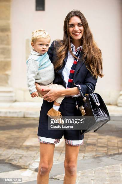 Guest, wearing a blue suit, blue and red necktie and black bag, is seen outside the Thom Browne show during Paris Fashion Week - Womenswear Spring...