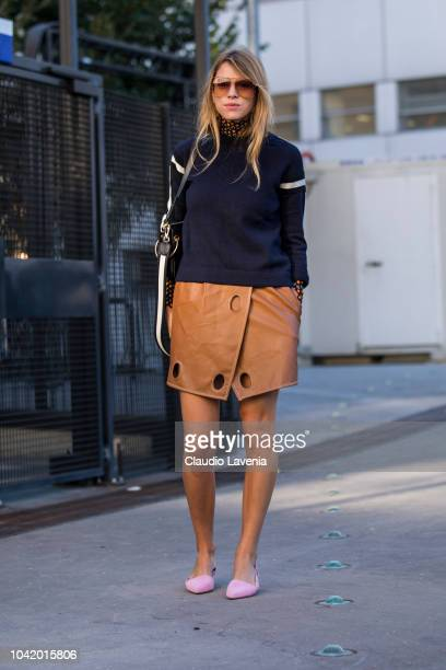 A guest wearing a blue sweater tan mini skirt and pink shoes is seen before the Chloe show on September 27 2018 in Paris France