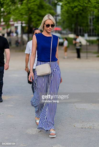A guest wearing a blue top and white blue striped pants outside Dries van Noten during the Paris Fashion Week Menswear Spring/Summer 2017 on June 23...