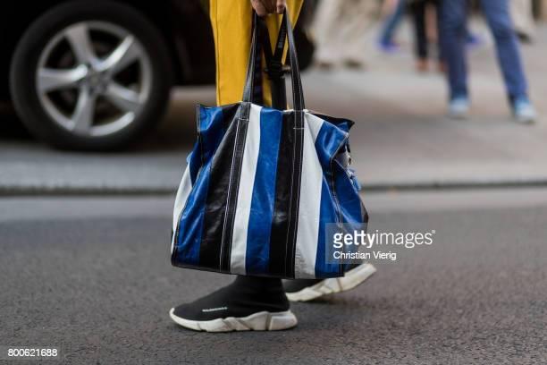 A guest wearing a blue white black striped Balenciaga bag Balenciaga sneakers outside Hermes during Paris Fashion Week Menswear Spring/Summer 2018...
