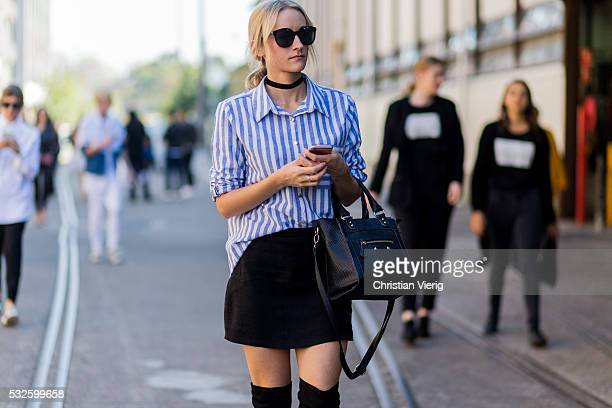 A guest wearing a blue white striped button shirt black choker mini skirt and Celine bag at MercedesBenz Fashion Week Resort 17 Collections at...