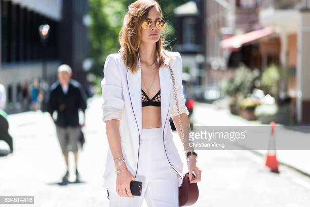 A guest wearing a bra and white blazer during the London Fashion Week Men's June 2017 collections on June 10 2017 in London England