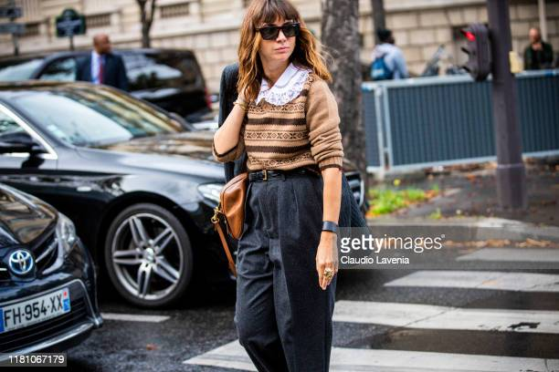 A guest wearing a brown jumper grey pants and tan bag is seen outside the Miu Miu show during Paris Fashion Week Womenswear Spring Summer 2020 on...