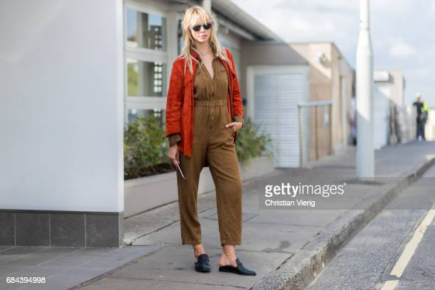 A guest wearing a brown jumpsuit outside Ten Pieces at day 5 during MercedesBenz Fashion Week Resort 18 Collections at Icebergs on May 18 2017 in...