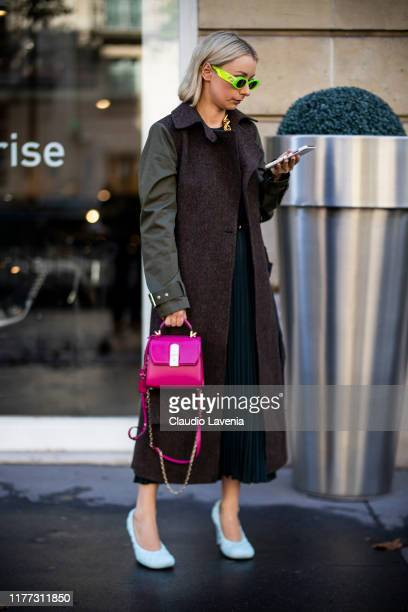 A guest wearing a brown long coat Bottega Veneta heels and fuchsia bag is seen outside the Faith Connexion show during Paris Fashion Week Womenswear...