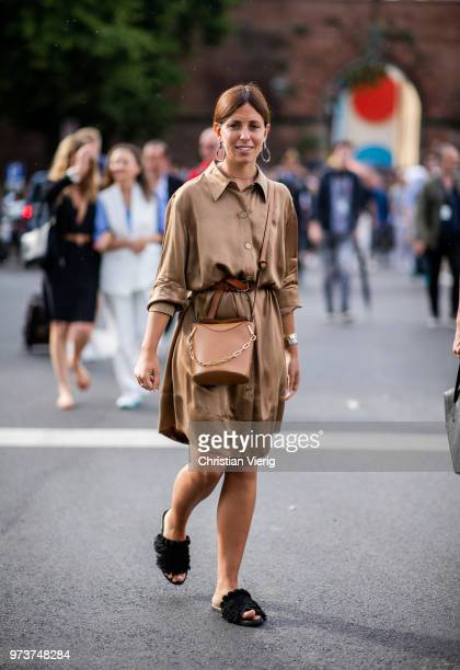A guest wearing a brown satin dress and bag is seen during the 94th Pitti Immagine Uomo on June 13 2018 in Florence Italy