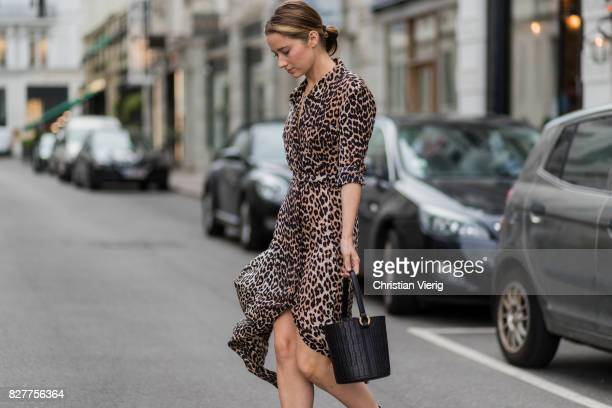 Guest wearing a bucket bag, dress with leopard print, silver heeled boots outside Designers Nest on August 8, 2017 in Copenhagen, Denmark.