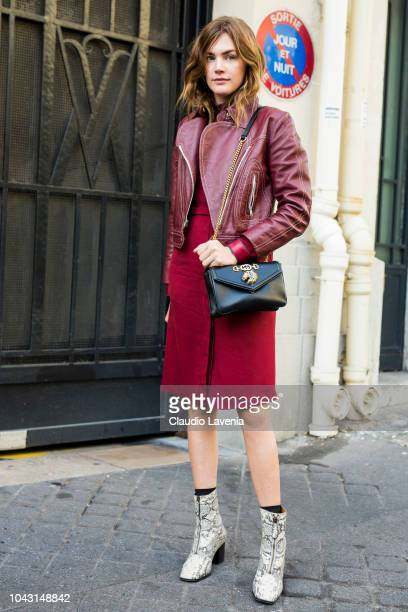 A guest wearing a burgundy leather jacket red midi skirt snake print ankle boots and black bag is seen before the Altuzarra show on September 29 2018...