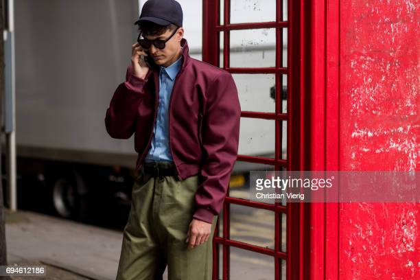 A guest wearing a cap and red bomber jacket during the London Fashion Week Men's June 2017 collections on June 10 2017 in London England