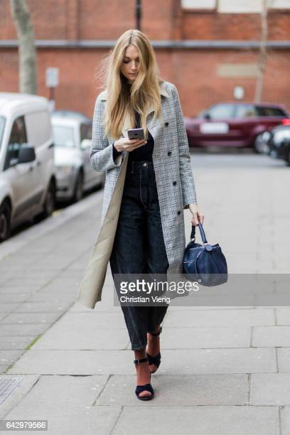 A guest wearing a checked coat blue Loewe bag dark denim jeans socks with heels outside Anya Hindmarch on day 3 of the London Fashion Week February...