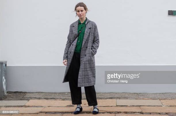 A guest wearing a checked coat green button shirt wide leg pants outside Baum Pferdgarten at the Copenhagen Fashion Week Autumn/Winter 17 on February...