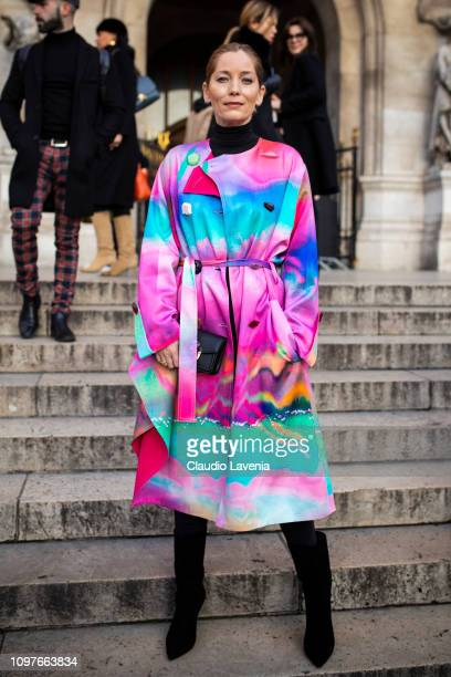 A guest wearing a colorful trench coat black boots and black bag is seen outside Schiaparelli during Paris Fashion Week Haute Couture Spring Summer...