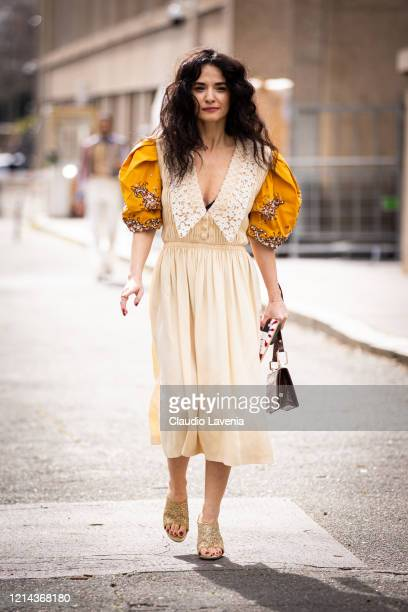 Guest, wearing a cream dress with yellow sleeves and gold mules, is seen outside Miu Miu, during Paris Fashion Week - Womenswear Fall/Winter...