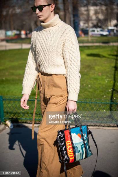 A guest wearing a cream sweater beige pants white boots and printed bag is seen outside Maison Margiela on Day 3 Paris Fashion Week Autumn/Winter...