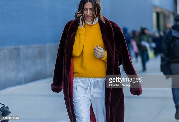 A guest wearing a dark red coat a yellow sweater and white jogger pants seen outside Lacoste during New York Fashion Week Women's Fall/Winter 2016 on...