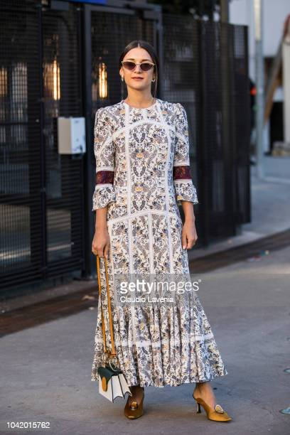 A guest wearing a decorated maxi dress white yellow and green bag and gold heels is seen before the Chloe show on September 27 2018 in Paris France