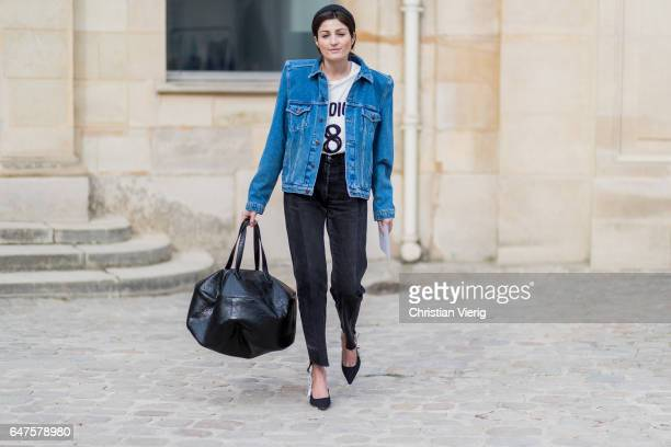 A guest wearing a denim jacket white knit black cropped pants oversized bag outside Dior on March 3 2017 in Paris France