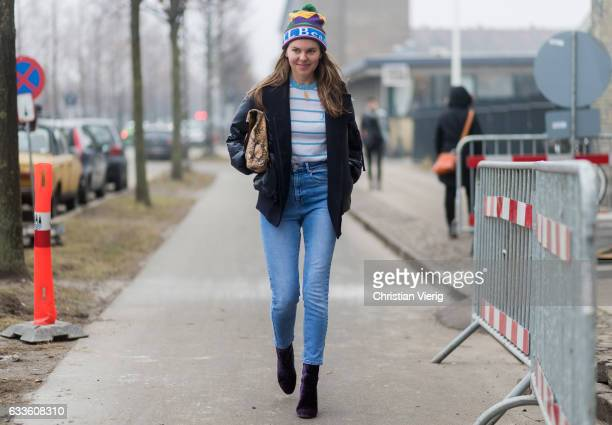 A guest wearing a denim jeans clutch with leo print multi colour beanie striped tshirt outside By Malene Birger during the Copenhagen Fashion Week...