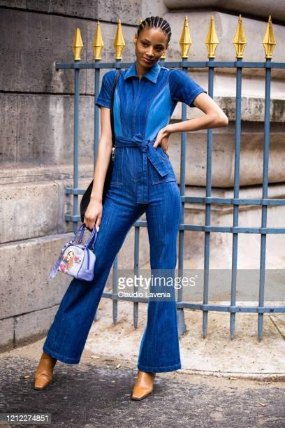 Guest, wearing a denim jumpsuit and purple printed bag, is seen outside Giambattista Valli, during Paris Fashion Week - Womenswear Fall/Winter...