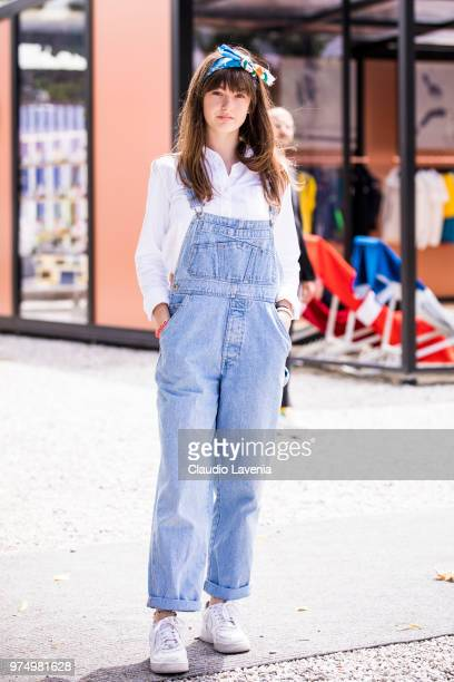 A guest wearing a denim overall and white shirt is seen during the 94th Pitti Immagine Uomo at Fortezza Da Basso on June 14 2018 in Florence Italy