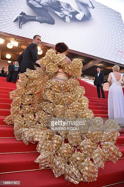 A guest wearing a dress made of biscuit trays arrives on May 17 2013 for the screening of the film 'The Past' presented in Competition at the 66th...