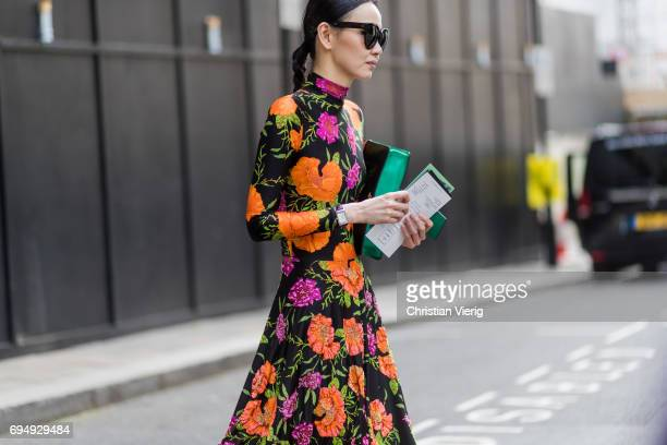 A guest wearing a dress with floral print during the London Fashion Week Men's June 2017 collections on June 11 2017 in London England