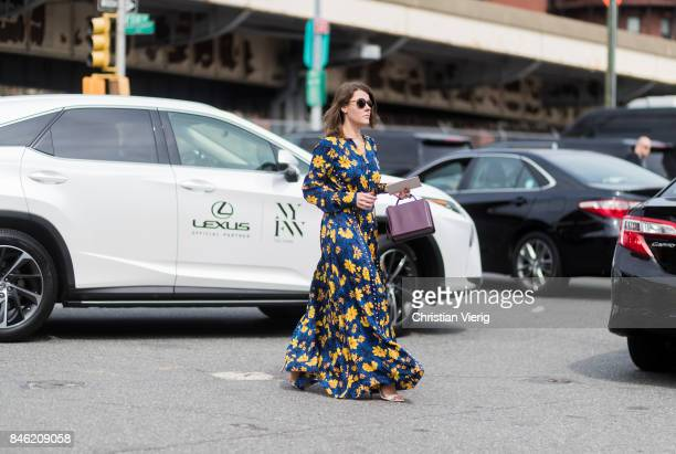 A guest wearing a dress with floral print in front of a Lexus seen in the streets of Manhattan outside Coach during New York Fashion Week on...