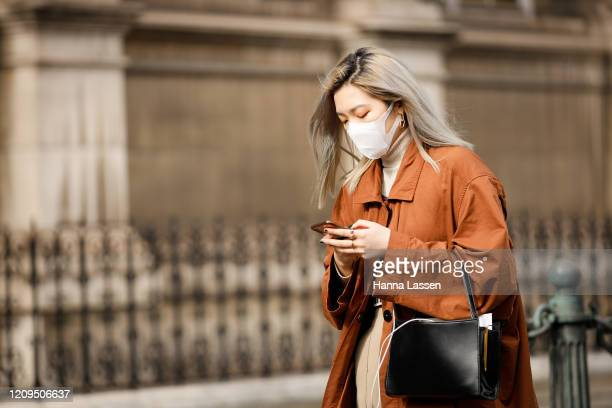 Guest wearing a face mask, tan orange trench outside Vivienne Westwood show during Paris Fashion week Womenswear Fall/Winter 2020/2021 Day Six on...