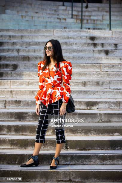 A guest wearing a floral print top black checked pants black bag and black shoes is seen outside Chanel during Paris Fashion Week Womenswear...