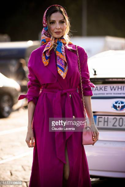 Guest, wearing a fuchsia trench coat, pink bag and printed head scarf, is seen outside the Tod's show during Milan Fashion Week Spring/Summer 2020 on...