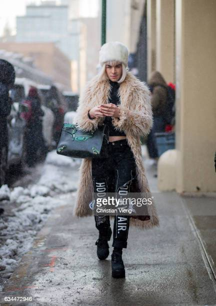A guest wearing a fur coat Balenciaga bag fur hat on February 9 2017 in New York City