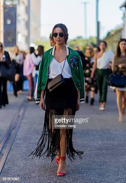 A guest wearing a green bomber jacket red heels and black skirt with fringes outside Bec Bridge at MercedesBenz Fashion Week Resort 17 Collections at...