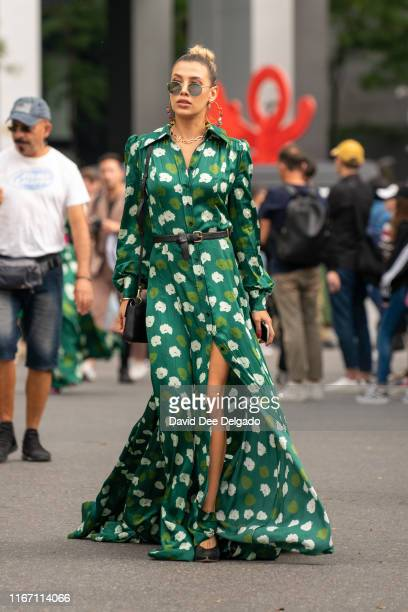 Guest wearing a green flower pattern dress, black belt, and round sunglasses attends the Carolina Herrera show during New York Fashion Week at the...
