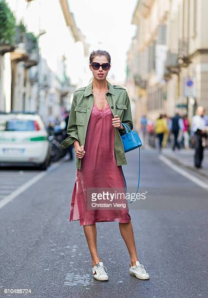 A guest wearing a green jacket and velvet dress and blue Prada bag during Milan Fashion Week Spring/Summer 2017 on September 25 2016 in Milan Italy