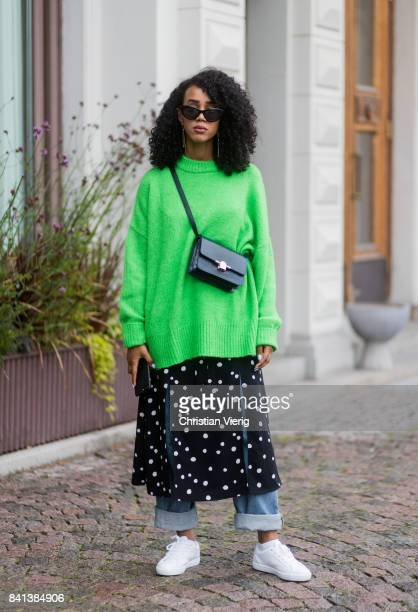 A guest wearing a green knit skirt over denim jeans sneaker outside Valerie on August 31 2017 in Stockholm Sweden