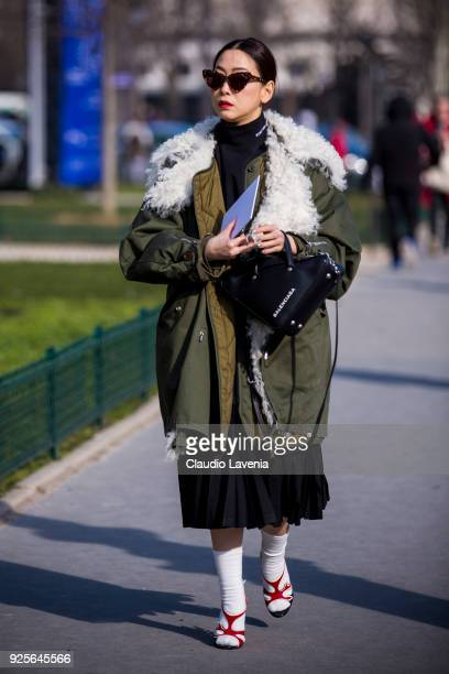 A guest wearing a green parka and a Balenciaga black bag is seen in the streets of Paris before the Maison Margiela show during Paris Fashion Week...