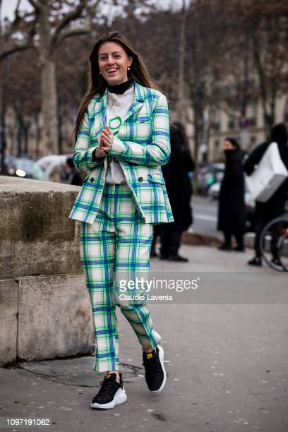 A guest wearing a green Sandro checked suit and black sneakers is seen in the streets of Paris before the Acne Femme show on January 20 2019 in Paris...