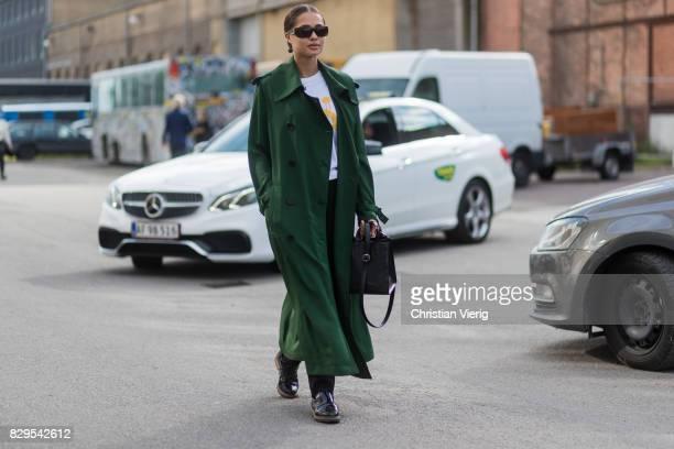 A guest wearing a green trench coat outside Ganni on August 10 2017 in Copenhagen Denmark